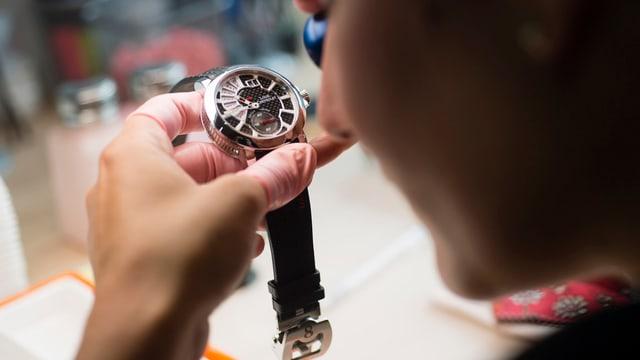 Eine Uhrenmacherin begutachtet eine neuangefertigte Uhr.