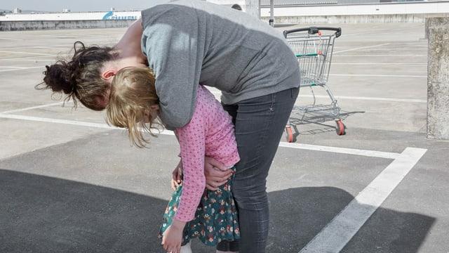 Eine Mutter umarmt ihr Kind von hinten.