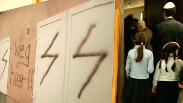 Eine Wand mit der Aufschrift «Weg hier!!», rechts ein Raum, in den jüdische Mädchen schreiten.
