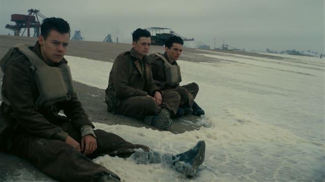 Drei Soldaten sitzen am Strand.