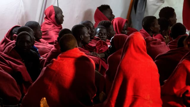 Migranten warten in Decken eingehüllt