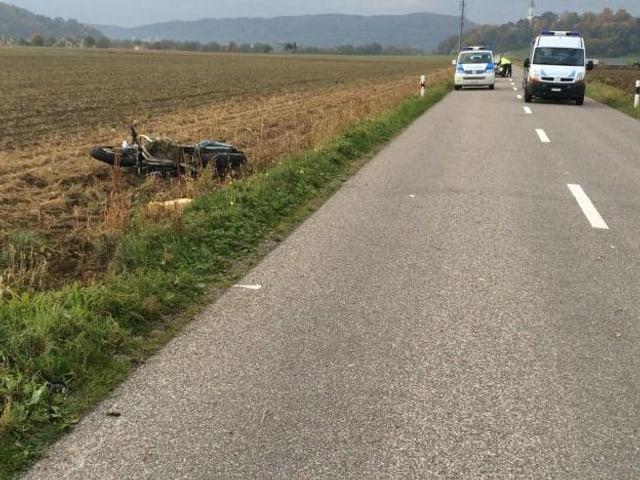 Motorrad liegt in Acker neben Strasse. Auf Strasse Unfallmarkierungen