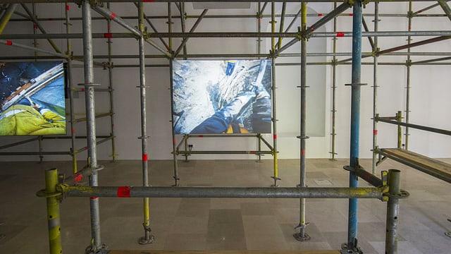 Eine Leinwand, die Bauarbeiten zeigt, ist an einem Baugerüst aufgehängt.