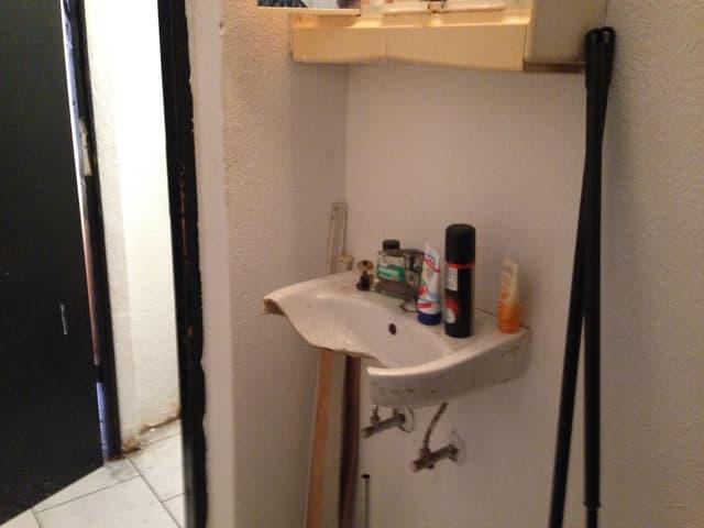 Ein abgebrochenes Waschbecken in einer dreckigen Wohnung.
