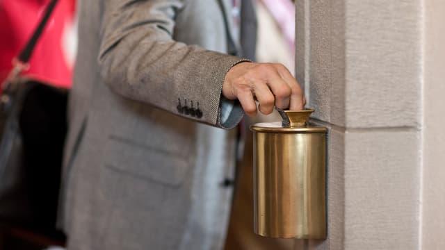 Ein Mann wirft beim Heraustreten aus der Kirche Geld mit seiner Hand in einen Behälter.
