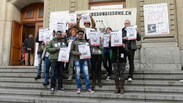 Asylsuchende und ihre Helfer stehen auf der Treppe vor der Kirche Saint-Laurent in Lausanne.