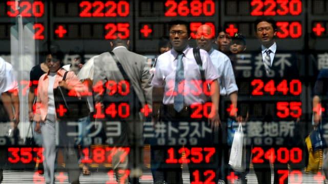 Asiatische Händler hinter Börsenzahlen.