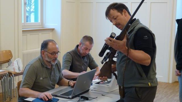 Daniel Bundi tegn ina buis da chatscha enta maun e legia la cifra da la buis. Werner Degonda sesa davos ina maisa e noda la cifra en in laptop.