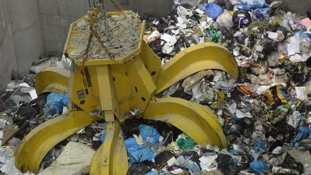 Ein Muellgreifer packt den Abfall in einer Kehrichtverbrennungsanlage.