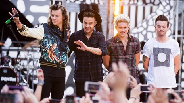 Harry Styles, Liam Payne, Niall Horan und Louis Tomlinson auf der Bühne, Hände von Fans im Vordergrund.