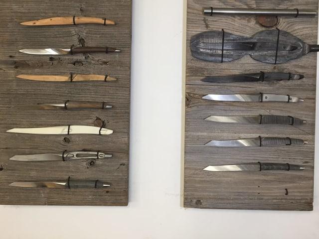 Rohlinge und Messer auf Holztafeln.