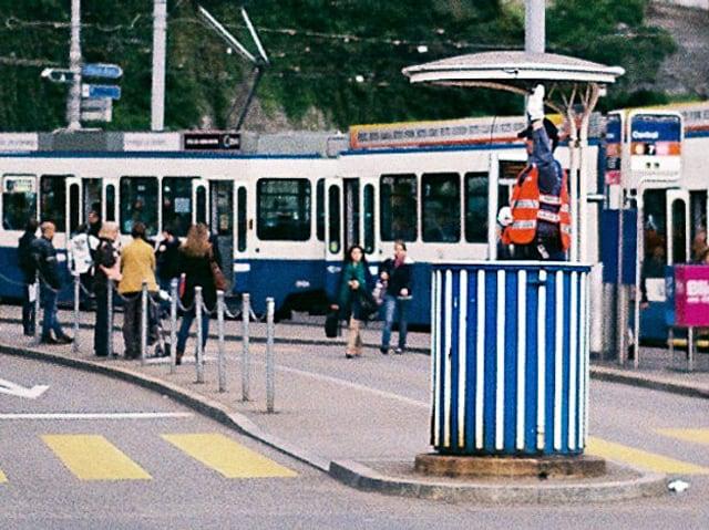 Ein Verkehrspolizist im gestreiften Häuschen am Central in Zürich, im Hintergrund ein Tram und Fussgänger.