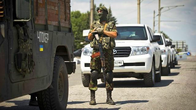 Ukrainischer Soldat vor OSZE-Fahrzeugen
