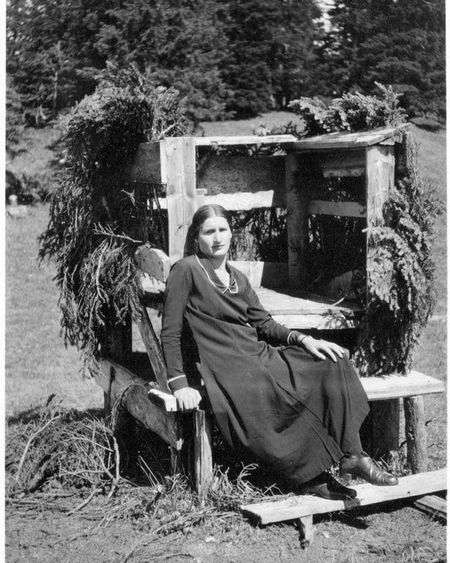 Schwarzweiss-Foto einer Frau auf Holzbank vor dem Wald.
