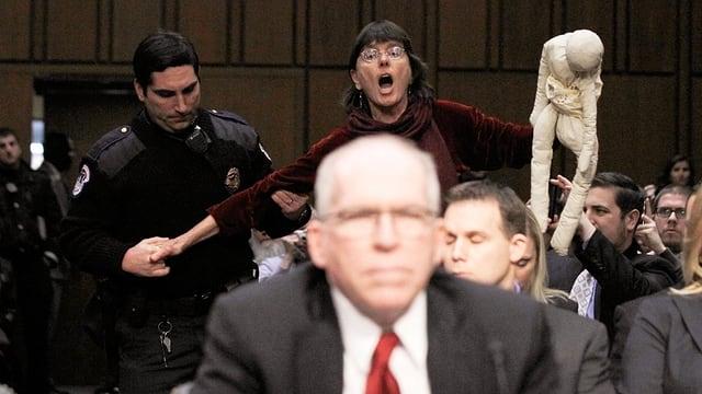 Brennan auf dem heissen Stuhl: Demonstrantin wird von der Polizei abgeführt.