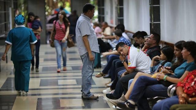 Menschen warten auf Stühlen in einem Spital, bis sie behandelt werden.