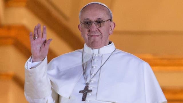 Papst Franziskus winkt den Gläubigen zu.