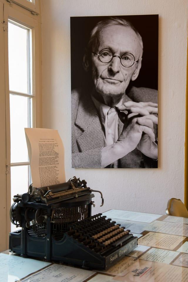 Ins vesa ina fotografia da Hermann Hesse pendì si en il museum Hermann Hesse a Montagnola e davant sin maisa ina maschina da scriver dal scriptur.