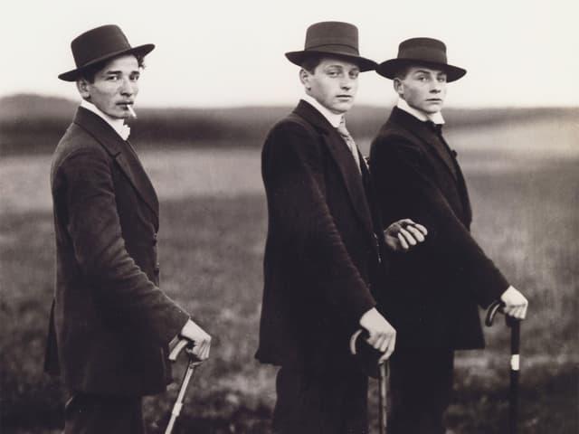 Man sieht drei Bauern, die elegant gekleidet sind. Sie halten alle einen Stock und tragen Hut.