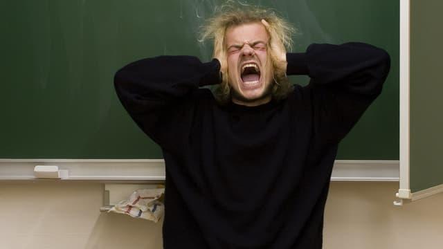 Ein Mann schreit vor einer Wandtafel.
