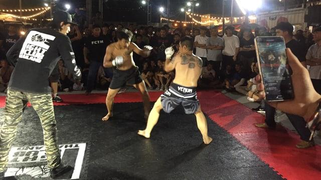 Zwei junge Männer mitten im Kampf ein Schiedsrichter in abwartender Haltung und eine Hand filmt den Kampf mit dem Handy.