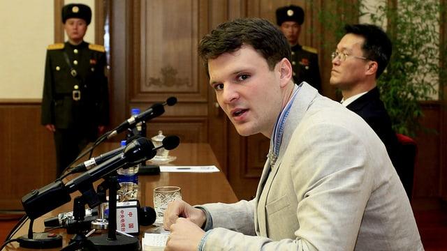 Der 21-jährige Student sitzt hinter Mikrofonen