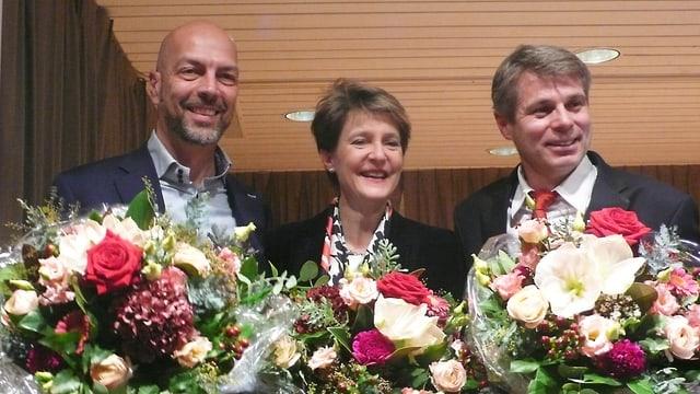 Die drei Personen stehen mit Blumensträussen da.