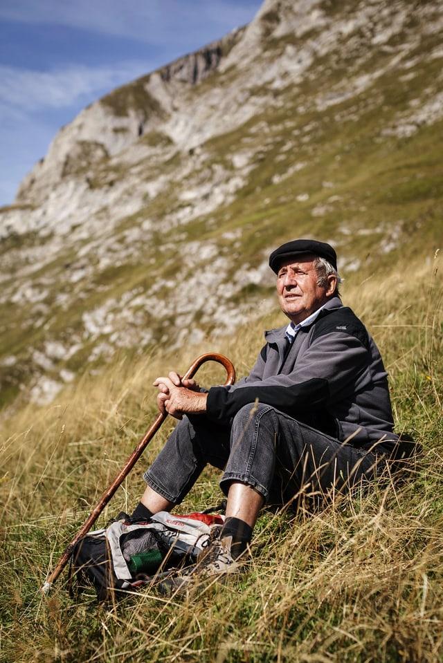 Mann sitzt mit Stock auf der Alp im Gras.