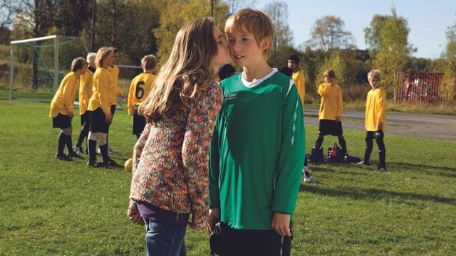 Mädchen küsst Junge auf dem Fussball-Platz