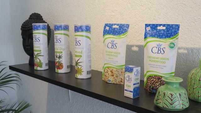 Auf einem Regal sind CBD-Produkte ausgestellt: Öl, Nahrungsmittelergänzungspulver.