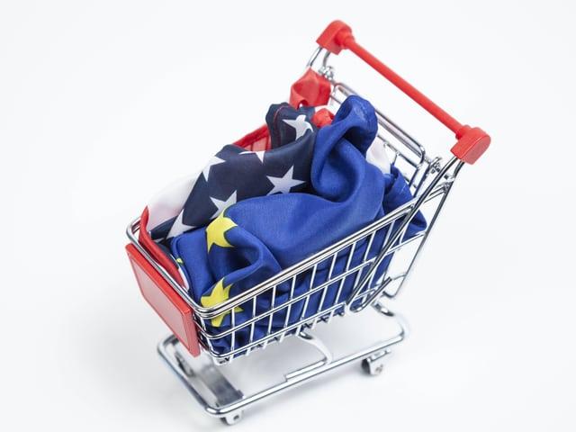 Ein Einkaufswagen mit einer EU- und einer US-Flagge darin.