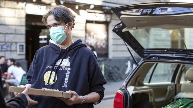 Eine Frau mit Schutzmaske verteilt Lebensmittel