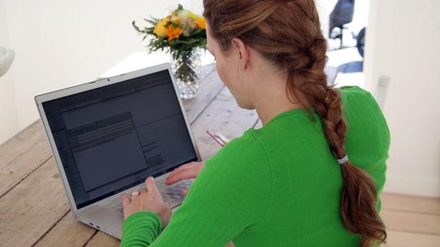 Eine Frau sitzt an einem Tisch und arbeitet an einem Notebook.