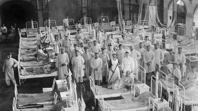 Schwarzweissaufnahme eines grossen Raums mit Stahlbetten, in dem sich Männern in weisser Krankenhauskleidung zu einem Gruppenbild formiert haben.