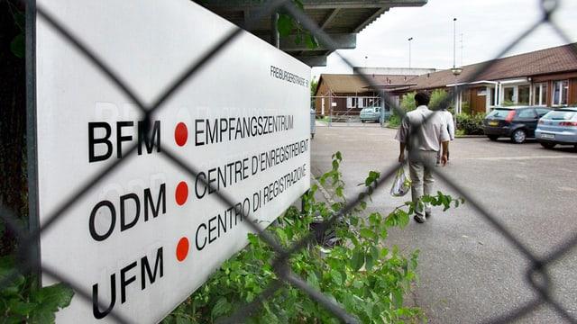 Bild des Empfangszentrums: Schild, Asylbewerber und Maschendrahtzaun