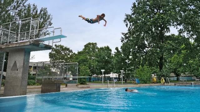 Bub springt ins Schwimmbecken