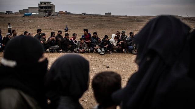 Irakische Männer sitzen in der Wüste.