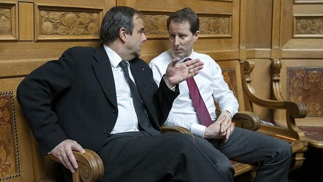 Pfister und Aeschi sitzen nebeneinader auf einer Bank im Nationalratssaal.