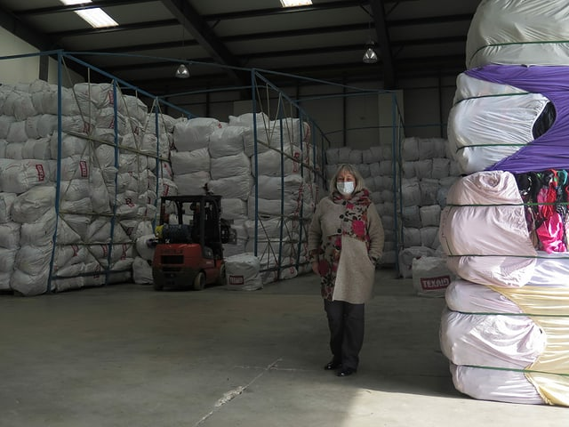 Eine Frau steht in einer Lagerhalle neben einem Turm aus gebrauchten Textilien.