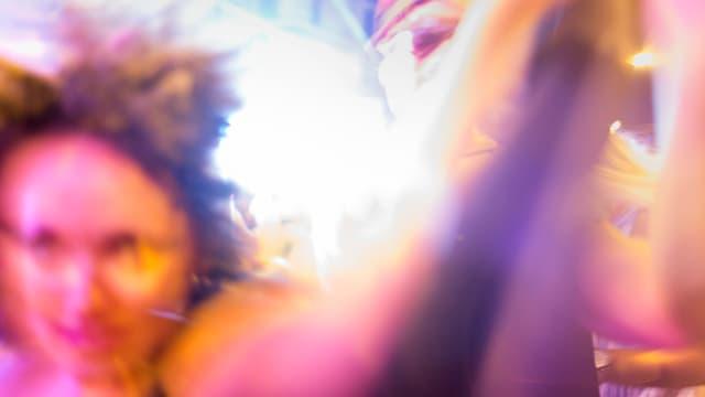 Ein verschwommenes, gelb-rosarotes Bild einer Partymeute.