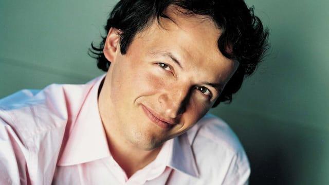 Der Dirigent Jean-Christophe Spinosi in rosa Hemd vor grünem Hintergrund.
