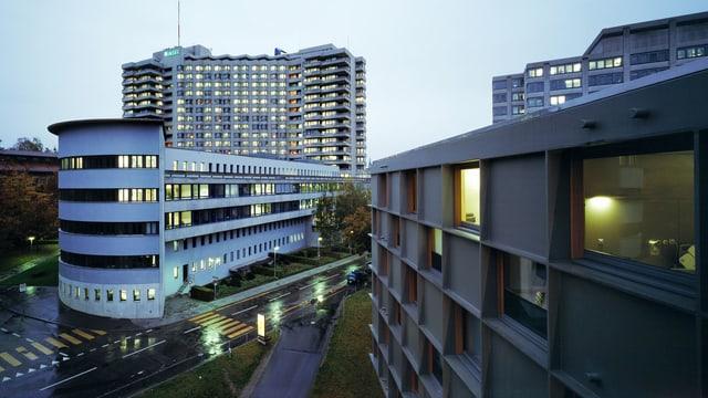 Das Inselspital in Bern bei Dämmerung, einzelne Fenster sind erleuchtet.