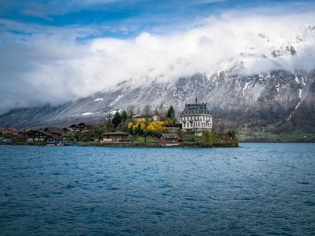 Blick über einen See auf ein Schloss, dahinter schroffe Felsen und steile Hänge mit frischem Schnee.
