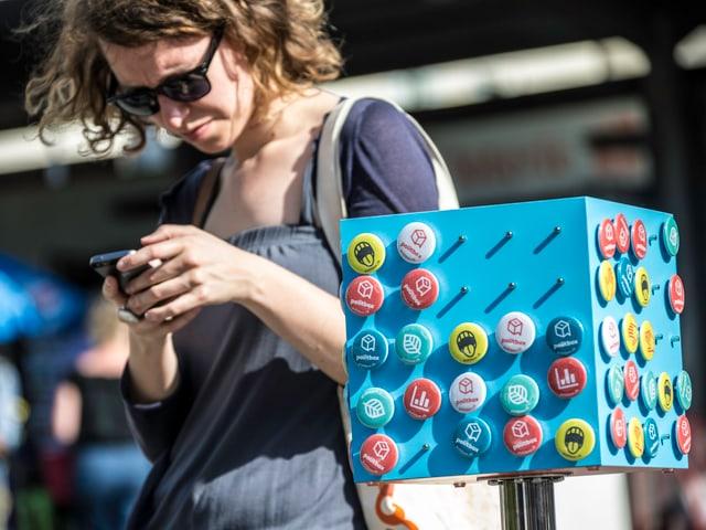 Eine junge Frau spielt politbox auf ihrem Smartphone.