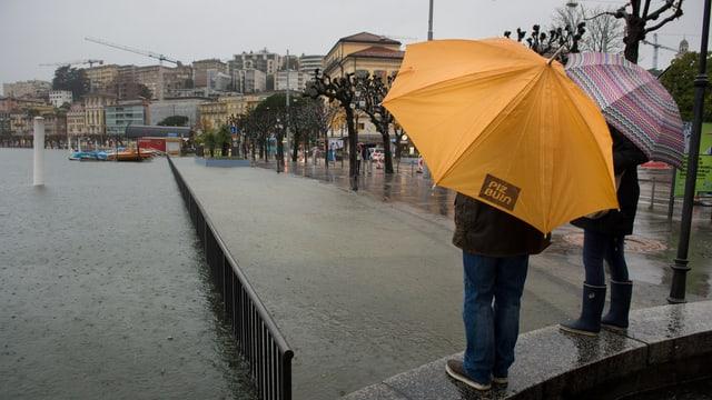 Touristen mit Regenschrimen am über die Ufer getretenen Lungolago von Lugano