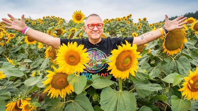 Ein Mann steht im Sonnenblumenfeld und streckt die Arme aus.