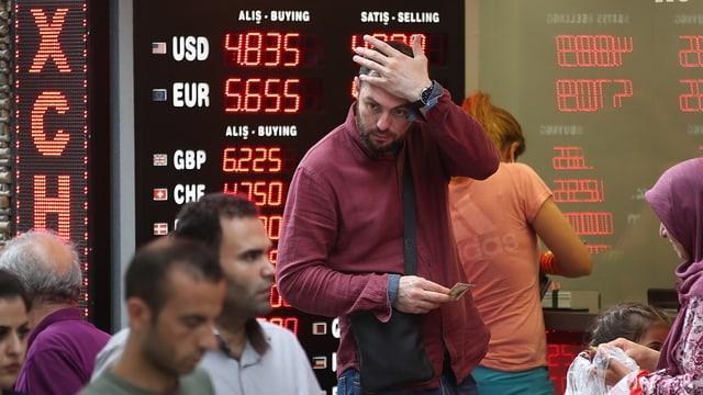Ein Mann greift sich vor einer Anzeigetafel für Wechselkurse an den Kopf.