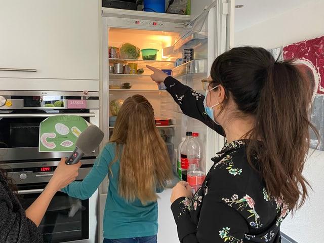 Annina und Ladina wählen Lebensmittel aus dem Kühlschrank aus.