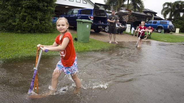 Mädchen mit Trotinett spielt vor einem überfluteten Haus.