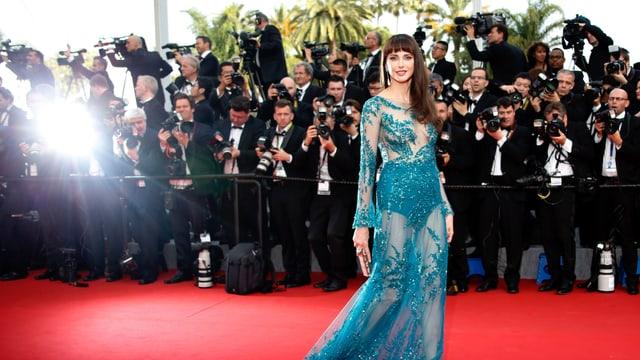 Eine Frau mit einem langen blauen Kleid auf dem roten Teppich, hinter ihr Fotografen.